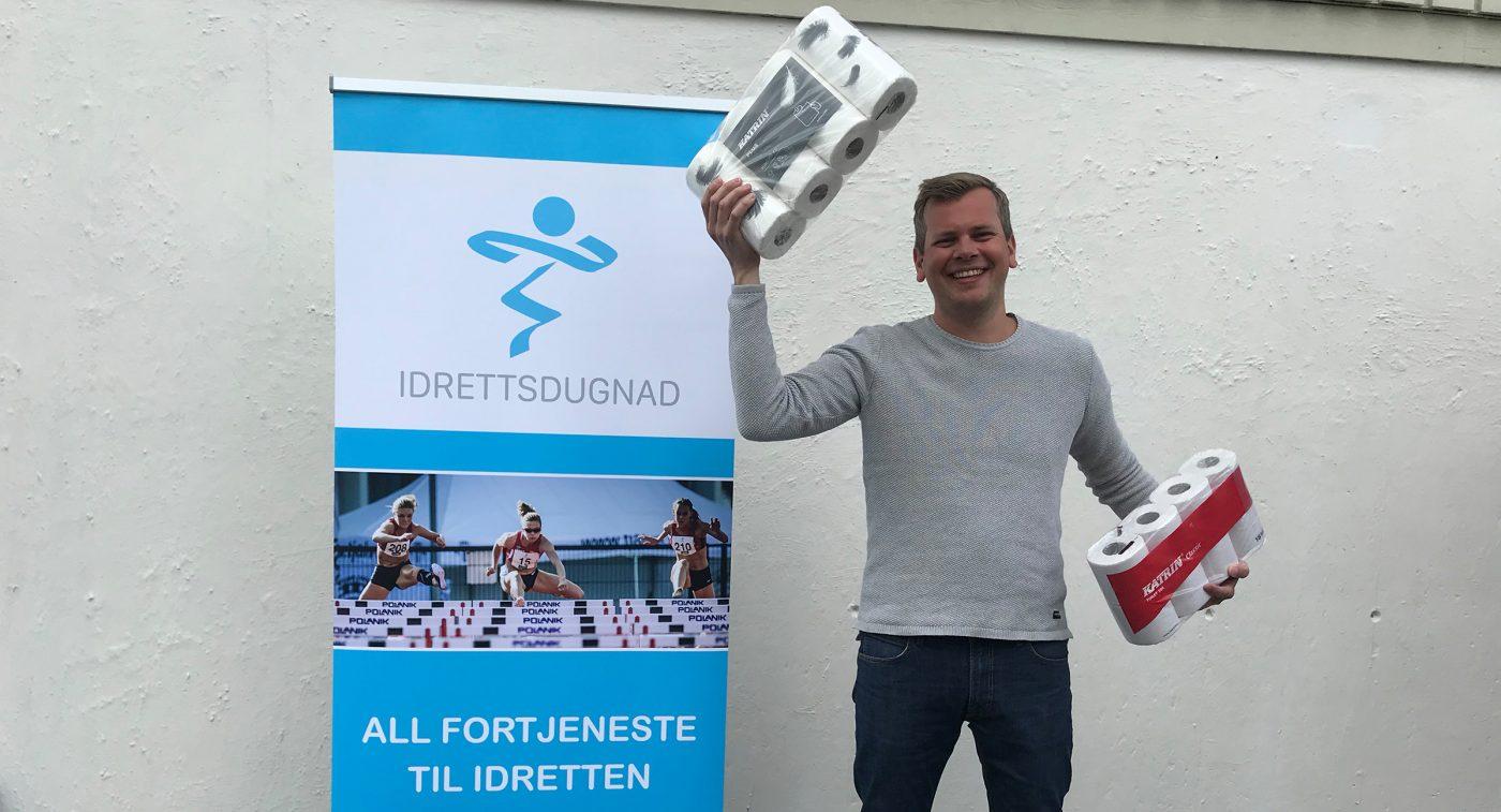 Daglig leder i Idrettsdugnad SA holder opp toalettpapir fra Katrin